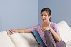 Retrato de la mujer que se sienta en el sofá en el país Foto de archivo