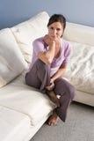 Retrato de la mujer que se sienta en el sofá en el país Imágenes de archivo libres de regalías