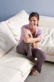 Retrato de la mujer que se sienta en el sofá en el país Imagenes de archivo