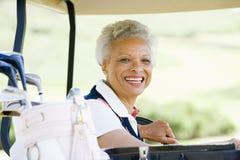 Retrato de la mujer que se sienta en un carro de golf Foto de archivo