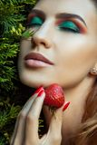 Retrato de la mujer que se sostiene cerca de la fresa dulce roja de la cara Imagen de archivo libre de regalías