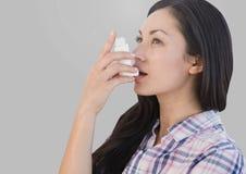 Retrato de la mujer que usa el inhalador del asma con el fondo gris Imágenes de archivo libres de regalías