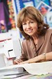 Retrato de la mujer que usa la máquina de coser eléctrica Foto de archivo