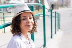 Retrato de la mujer de la raza mixta en el cuadrado urbano, verjas verdes Fotografía de archivo