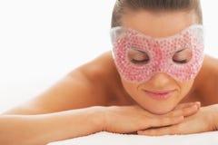 Retrato de la mujer relajada en la máscara de ojo que pone en la tabla del masaje fotos de archivo