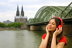 Retrato de la mujer relajada joven que escucha la música con el fondo urbano Muchacha de la ciudad con el auricular rojo que disf Foto de archivo libre de regalías