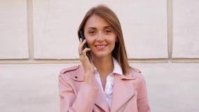 Retrato de la mujer de risa joven que habla en el teléfono móvil almacen de video