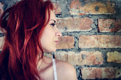 Retrato de la mujer roja contra la pared de ladrillo al aire libre Fotos de archivo