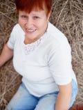 Retrato de la mujer roja madura sonriente del pelo en heno Fotos de archivo