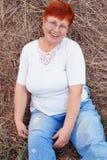 Retrato de la mujer roja madura sonriente del pelo en heno Imagenes de archivo