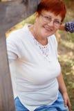Retrato de la mujer roja madura sonriente del pelo en jardín Imagenes de archivo