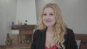 Retrato de la mujer rubia adorable con el pelo rizado en desgaste formal que habla delante de la cámara en el cuarto con moderno metrajes