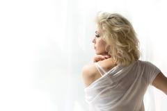 Retrato de la mujer rubia adulta que mira la ventana imágenes de archivo libres de regalías