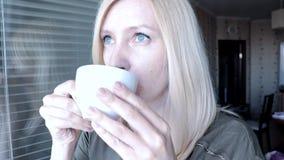 Retrato de la mujer rubia atractiva bonita joven con los ojos azules que se colocan cerca de la ventana abierta por la ma?ana, be almacen de video