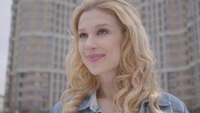 Retrato de la mujer rubia confiada sonriente bonita que habla con el interlocutor irreconocible delante del rascacielos Urbano metrajes
