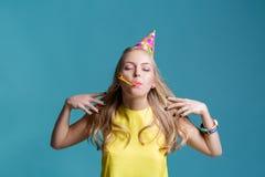 Retrato de la mujer rubia divertida en sombrero del cumpleaños y camisa amarilla en fondo azul Celebración y partido Imagen de archivo