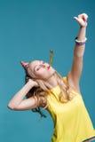 Retrato de la mujer rubia divertida en sombrero del cumpleaños y camisa amarilla en fondo azul Celebración y partido Imagenes de archivo
