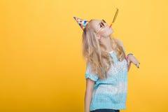 Retrato de la mujer rubia divertida en sombrero del cumpleaños y camisa azul en fondo amarillo Celebración y partido Fotografía de archivo