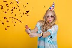 Retrato de la mujer rubia divertida en sombrero del cumpleaños y del confeti rojo en fondo amarillo Celebración y partido Imágenes de archivo libres de regalías