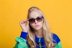 Retrato de la mujer rubia hermosa en gafas de sol y chaqueta con capucha del verde azul en fondo amarillo Verano del inconformist Fotos de archivo