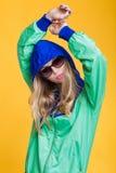 Retrato de la mujer rubia hermosa en gafas de sol y chaqueta con capucha del verde azul en fondo amarillo Verano del inconformist Fotografía de archivo libre de regalías