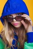 Retrato de la mujer rubia hermosa en gafas de sol y chaqueta con capucha del verde azul en fondo amarillo Verano del inconformist Foto de archivo