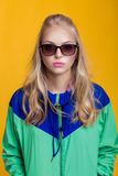 Retrato de la mujer rubia hermosa en gafas de sol y chaqueta con capucha del verde azul en fondo amarillo Verano del inconformist Imágenes de archivo libres de regalías