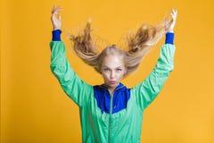 Retrato de la mujer rubia hermosa en gafas de sol y chaqueta verde azul en fondo amarillo Verano del inconformista Imágenes de archivo libres de regalías