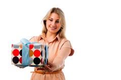 Retrato de la mujer rubia hermosa joven que sostiene la caja de regalo aislada en el fondo blanco Imagenes de archivo