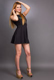 Retrato de la mujer rubia joven atractiva que lleva un mini vestido negro foto de archivo