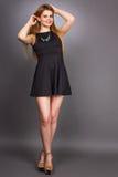 Retrato de la mujer rubia joven atractiva que lleva un mini vestido negro imagen de archivo