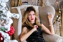 Retrato de la mujer rubia joven con un vidrio de champán que se sienta en una silla delante del árbol del Año Nuevo Foto de archivo