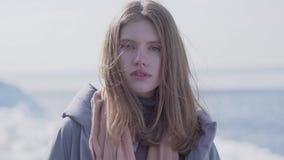 Retrato de la mujer rubia joven confiada adorable con el pelo largo y los ojos azules que miran en la cámara Mujer atractiva de metrajes