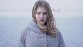 Retrato de la mujer rubia joven confiada linda con el pelo largo y los ojos azules que miran en la cámara Mujer atractiva de metrajes