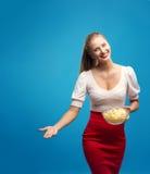 Retrato de la mujer rubia joven de moda en el vestido rosado, tenencia brillante del maquillaje, comiendo la patata frita, microp Imágenes de archivo libres de regalías