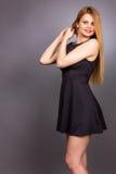 Retrato de la mujer rubia joven feliz que lleva un mini vestido negro Foto de archivo