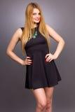 Retrato de la mujer rubia joven feliz que lleva un mini vestido negro fotos de archivo libres de regalías