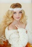 Retrato de la mujer rubia joven muy linda en un suéter de punto blanco Foto de archivo libre de regalías