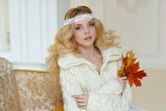 Retrato de la mujer rubia joven muy linda en un suéter de punto blanco Imagen de archivo