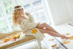 Retrato de la mujer rubia joven muy linda en un suéter de punto blanco Fotografía de archivo