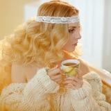Retrato de la mujer rubia joven muy linda en un suéter de punto blanco Imagen de archivo libre de regalías