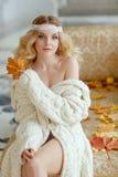 Retrato de la mujer rubia joven muy linda en un suéter de punto blanco Imágenes de archivo libres de regalías
