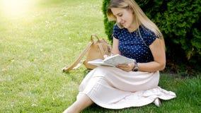 Retrato de la mujer rubia joven que se sienta debajo de parque de AR del árbol y que escribe en diario Fotografía de archivo