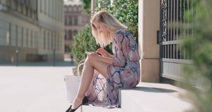 Retrato de la mujer rubia joven que usa la tableta almacen de video