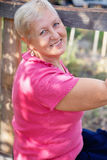 Retrato de la mujer rubia madura sonriente en jardín Imagen de archivo