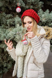 Retrato de la mujer rubia, ornamentos colgantes de la Navidad en picea Imagenes de archivo