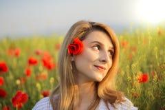 Retrato de la mujer rubia que se coloca en el campo de amapolas Imagen de archivo