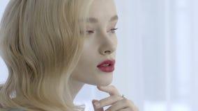 Retrato de la mujer rubia sensual con los labios rojos en el fondo blanco