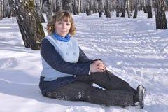 Retrato de la mujer rusa que se sienta en nieve en la madera de abedul Imágenes de archivo libres de regalías