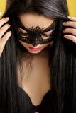Retrato de la mujer sensual hermosa en máscara negra del cordón en fondo amarillo Muchacha atractiva en la máscara veneciana fotografía de archivo libre de regalías